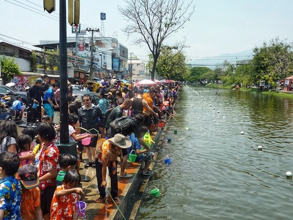 Hundreds of people gather around a moat.
