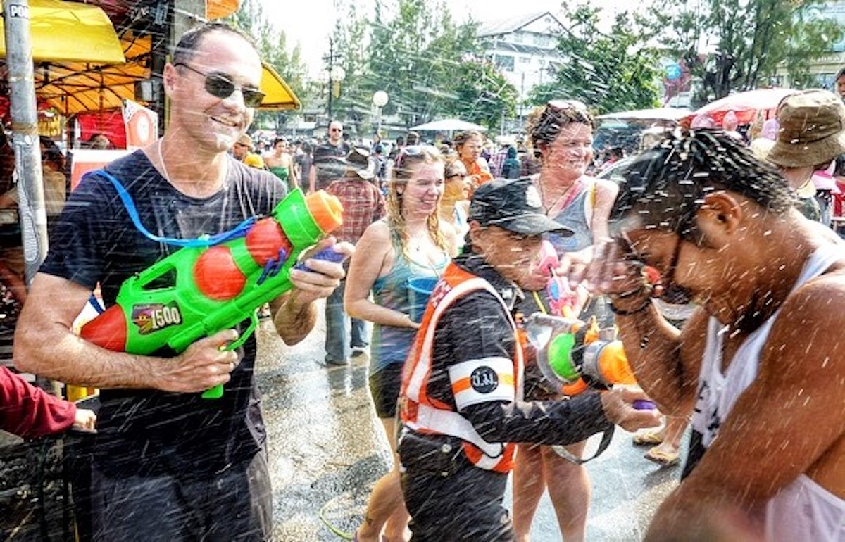 A policewoman laughs as people have a water fight.