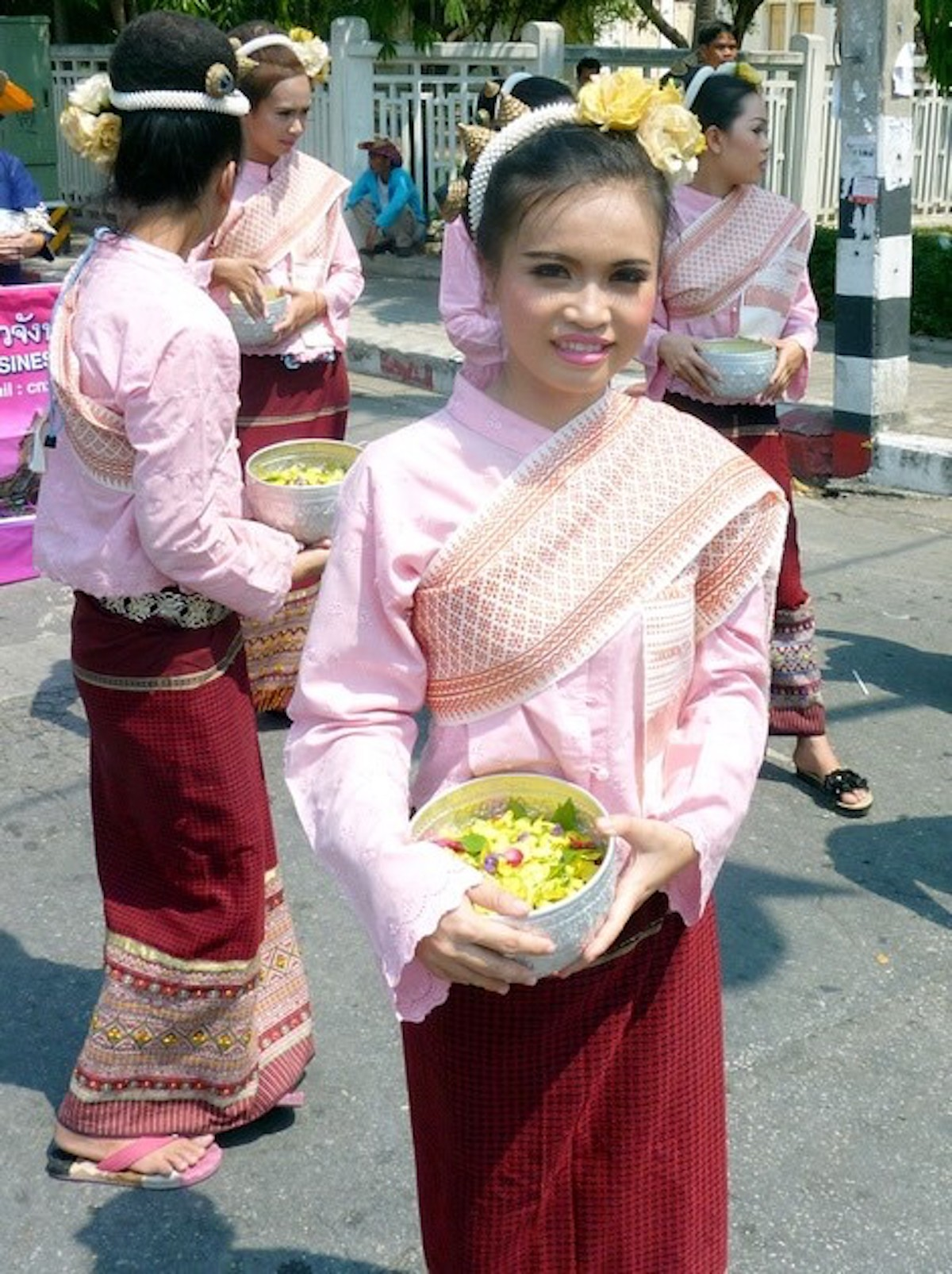A pretty Thai lady in traditional dress smiles at the camera