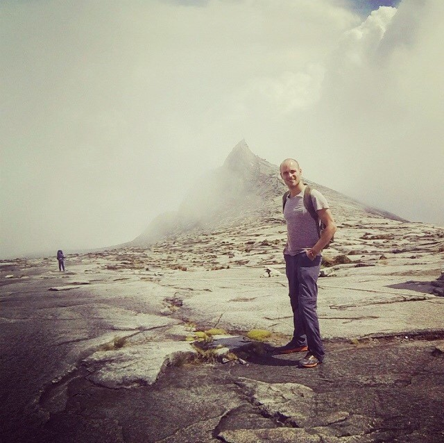 man standing in front of mountain peak