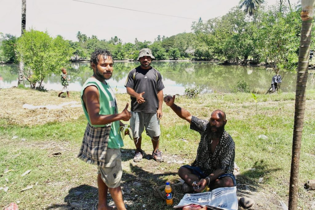 3 local men smile in Papua New Guinea