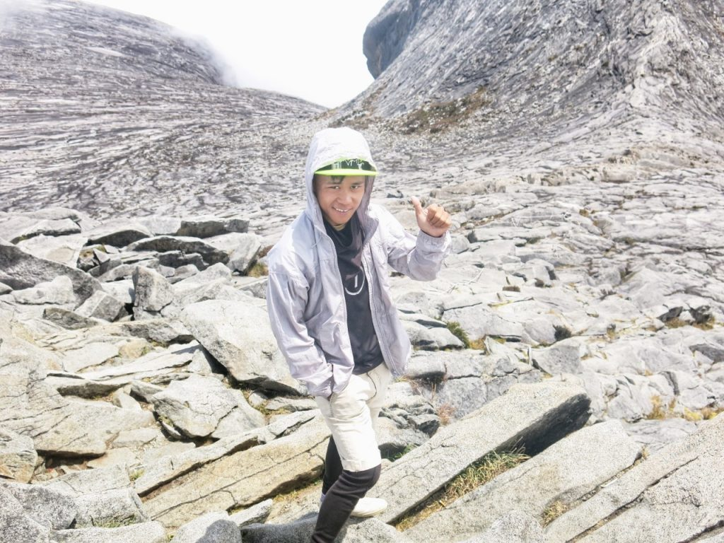 Man gives thumbs up on a mountain