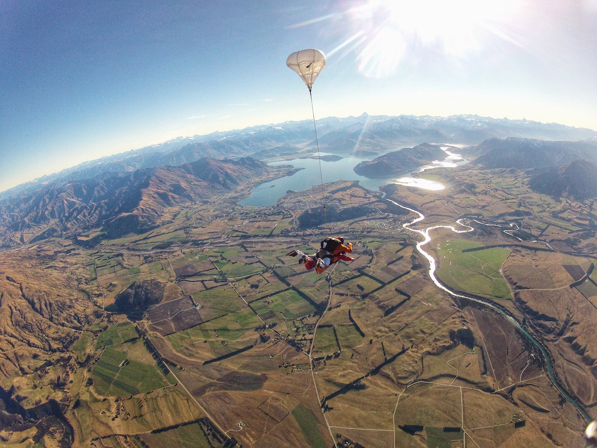 Tandem skydive above lush scenery on a sunny day.