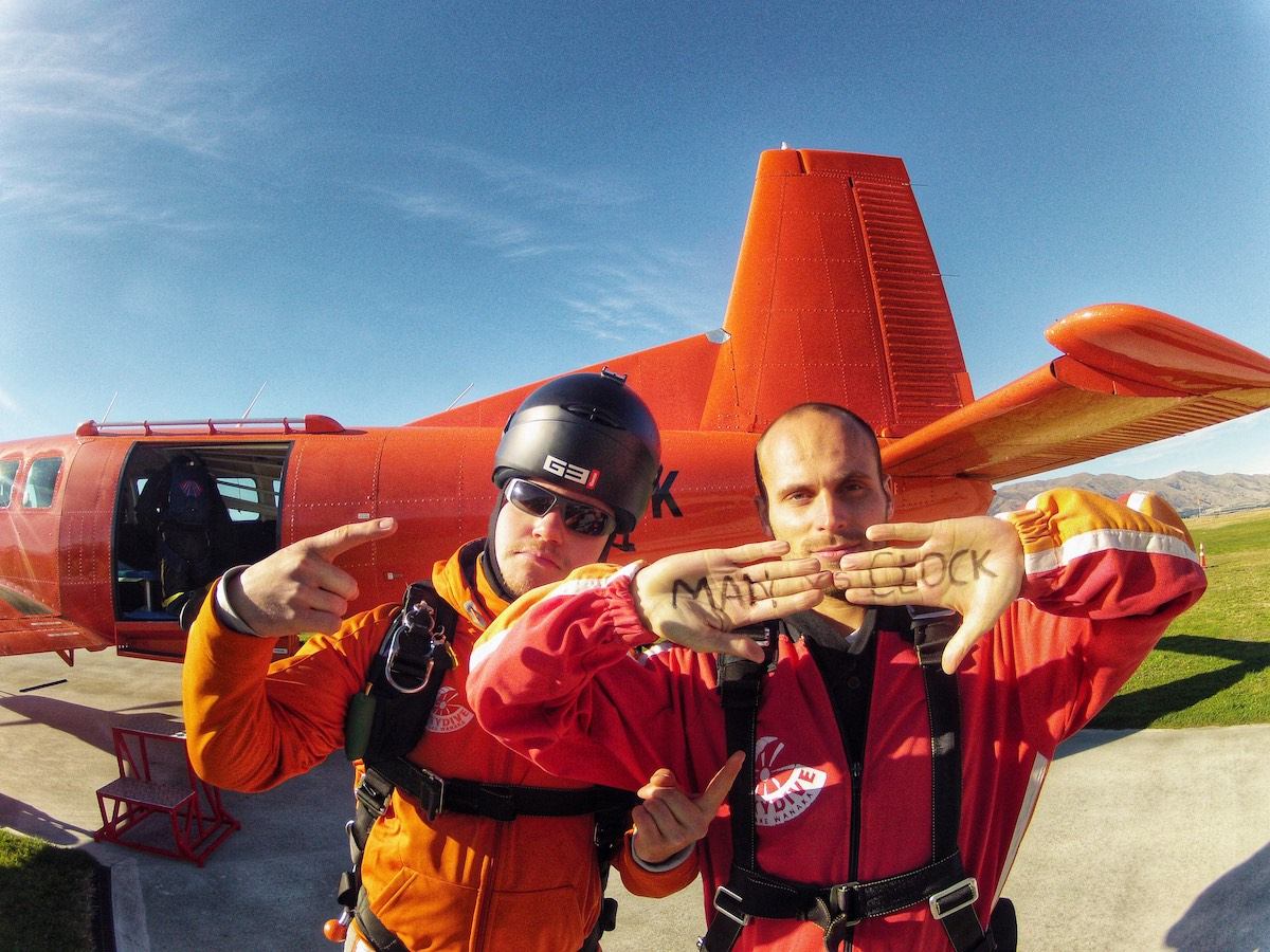 2 men standing outside of a skydiving plane.