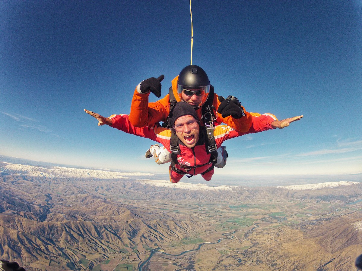 2 men pose for the camera during a skydive.
