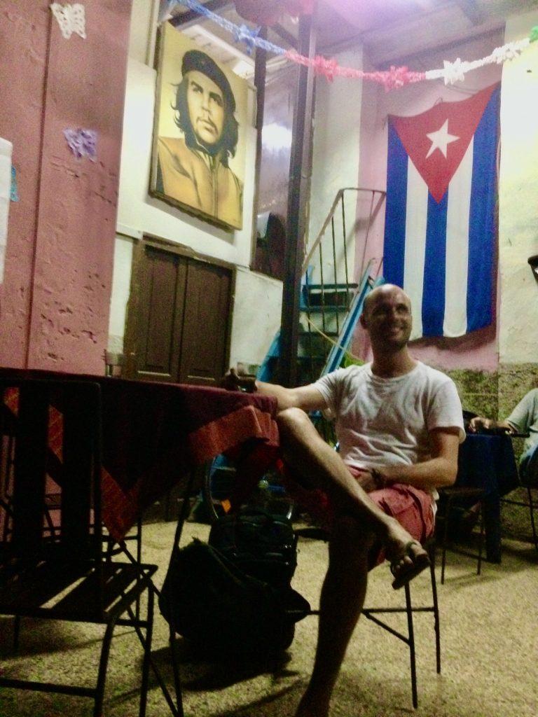 Man sits in front of Che Guevara and Cuban flag at a bar