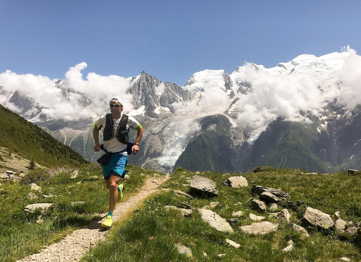 Man running with striking mountain backdrop.