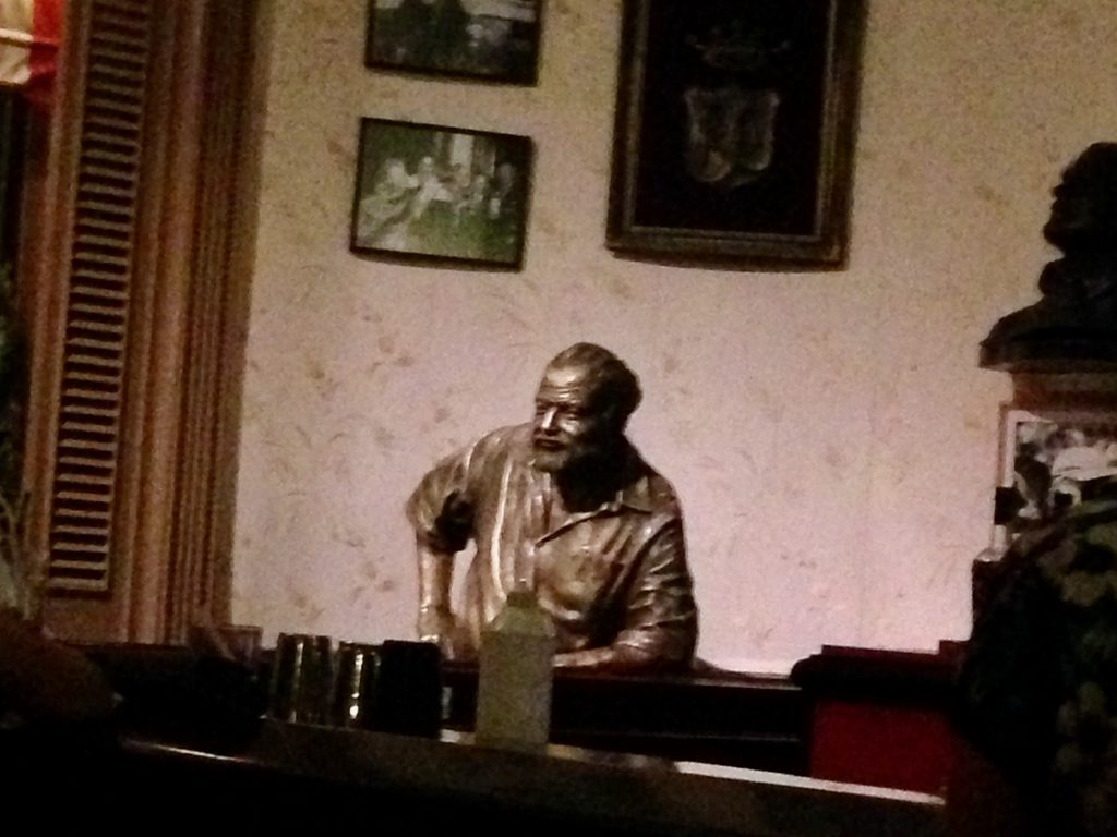 Status of Ernest Hemmingway rest against a bar.
