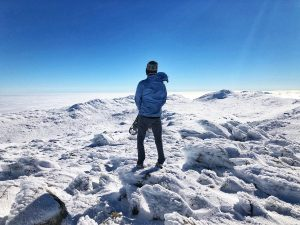 Man standing on top of Mount Kosciuszko on a snowy day.