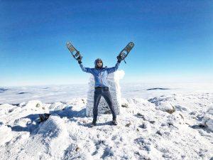 Man raising arms on top of snowy mountain.