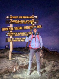 Smiling man standing on top of Mount Kilimanjaro.