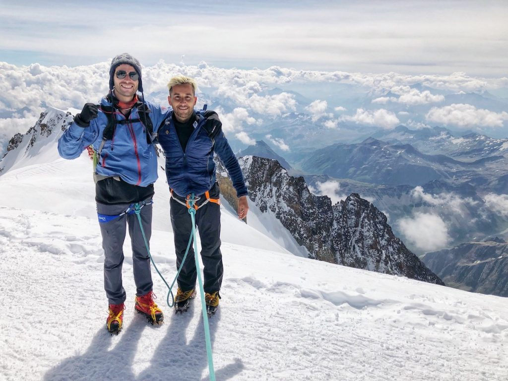 two men standing on top of a snowy mountain.