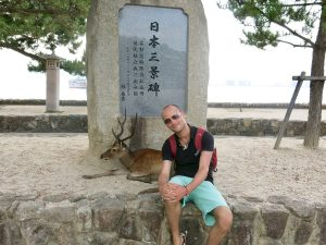 Tourist poses with deer in national park