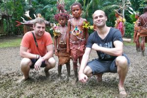 Male tourists with young tribespeople in Papua New Guinea